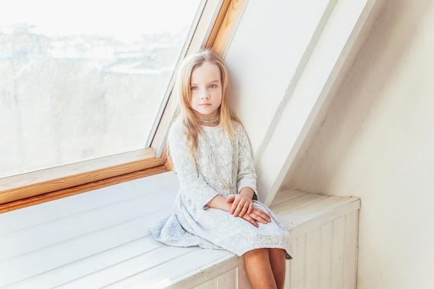 Bądź w domu bądź bezpieczny. mała śliczna słodka uśmiechnięta dziewczyna w biel sukni obsiadaniu na parapecie w jaskrawym lekkim żywym pokoju w domu indoors. dzieci w wieku szkolnym młodzież relaks koncepcja.