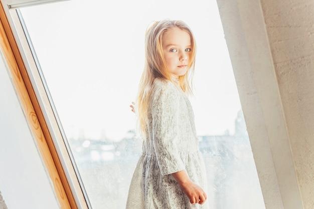Bądź w domu bądź bezpieczny. mała śliczna słodka uśmiechnięta dziewczyna w biel sukni pozyci na parapecie w jaskrawym lekkim żywym pokoju w domu indoors. dzieci w wieku szkolnym młodzież relaks koncepcja.