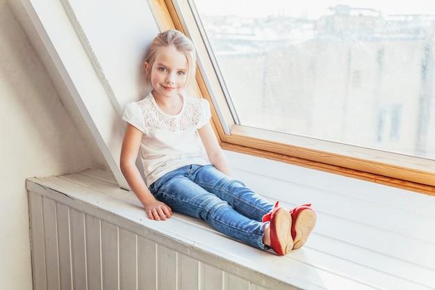 Bądź w domu bądź bezpieczny. mała śliczna słodka uśmiechnięta dziewczyna w cajgach i białym t-shirt siedzi na parapecie w jasnym świetle salonu w domu w pomieszczeniu. dzieci w wieku szkolnym młodzież relaks koncepcja.