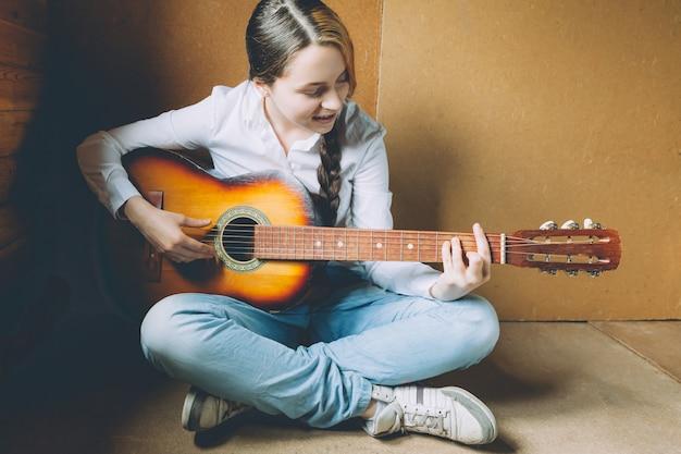Bądź w domu bądź bezpieczny. młoda kobieta siedzi w pokoju na podłodze i gra na gitarze w domu. teen dziewczyna uczy się grać piosenki i pisać muzykę. hobby styl życia relaks koncepcja edukacji wypoczynek instrument.