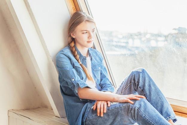 Bądź w domu bądź bezpieczny. młoda śliczna nastolatka w dżinsach, dżinsowej kurtce i białej koszulce siedzi na parapecie w jasnym jasnym salonie w domu w domu i myśli. koncepcja jomo odległości społecznej.