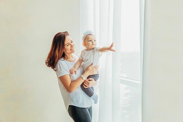 Bądź w domu bądź bezpieczny. potomstwa matkują trzymać jej dziecka. kobiety i niemowlaka mała dziewczynka relaksuje w białej sypialni blisko windiow indoors. szczęśliwa rodzina w domu. młoda mama gra z córką.