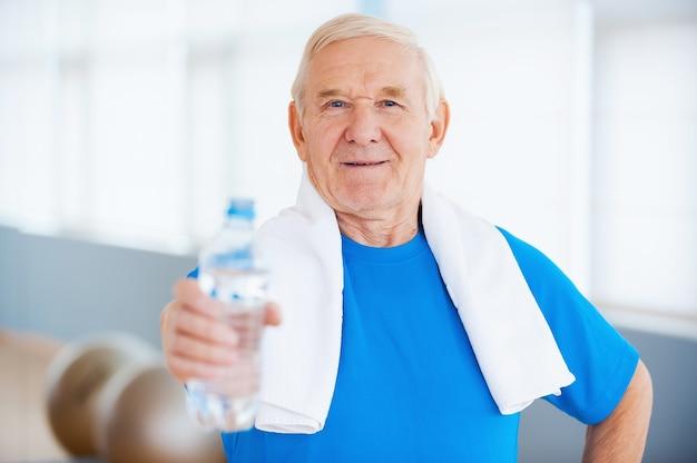 Bądź zdrów! szczęśliwy starszy mężczyzna z ręcznikiem na ramionach wyciągający butelkę z wodą stojąc w klubie fitness