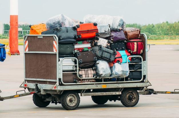 Bagaż lotniskowy wózek z walizkami przed załadowaniem na pokład samolotu.