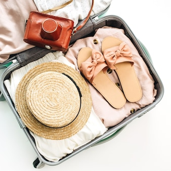Bagaż podręczny z letnie ubrania kobiece i retro kamera na białym tle. płaski układanie, widok z góry