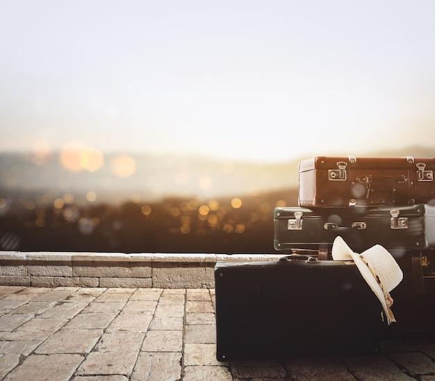 Bagaż spoczywający na starym kamiennym chodniku na tle panoramy o zachodzie słońca