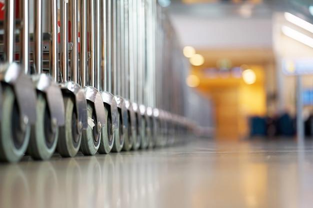 Bagaż wózków na surowym lotnisku. widok z bliska wózki bagażu na lotnisku. wózki bagażowe na nowoczesnym lotnisku. selektywne ustawianie ostrości.