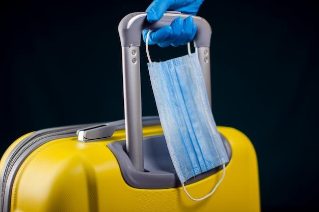Bagaż z medyczną maską na twarz. ręka w rękawiczkach medycznych trzymając bagaż. koncepcja podróży i koronawirusa.