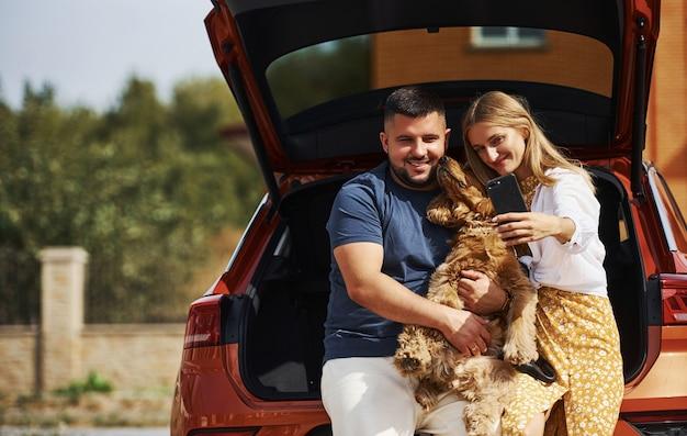 Bagażnik jest otwarty. urocza para spaceruje z psem na zewnątrz w pobliżu samochodu.