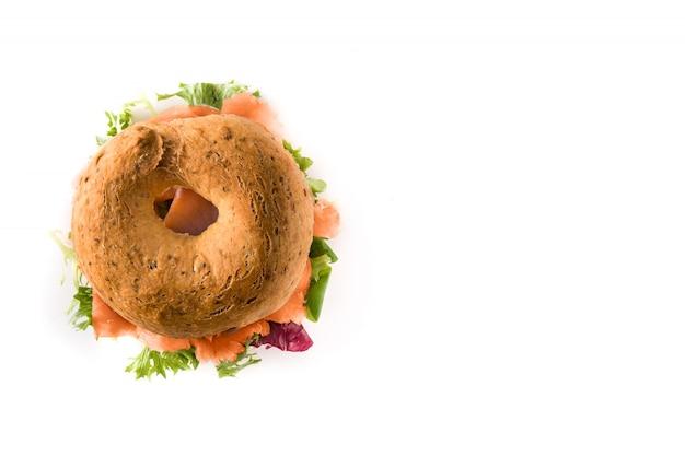 Bagelowa kanapka z kremowym serem, wędzonym łososiem i warzywami odizolowywającymi na bielu, kopii przestrzeń