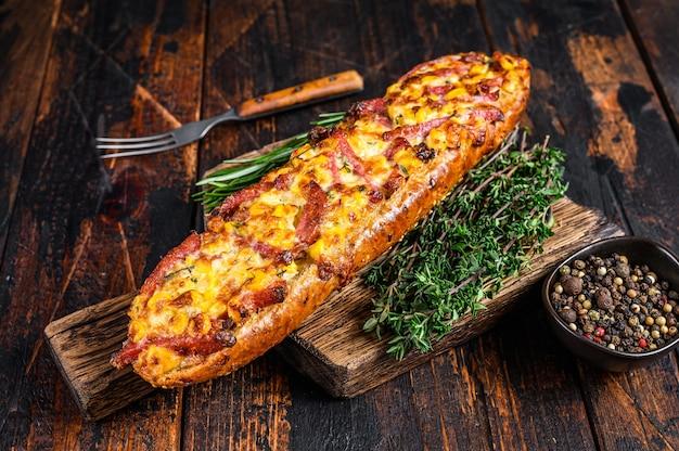 Bagietka faszerowana szynką, boczkiem, warzywami i serem na desce. ciemne tło drewniane. widok z góry.
