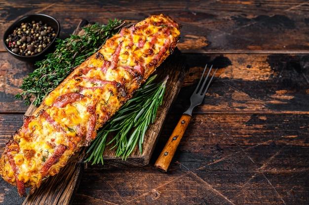 Bagietka faszerowana szynką, boczkiem, warzywami i serem na desce