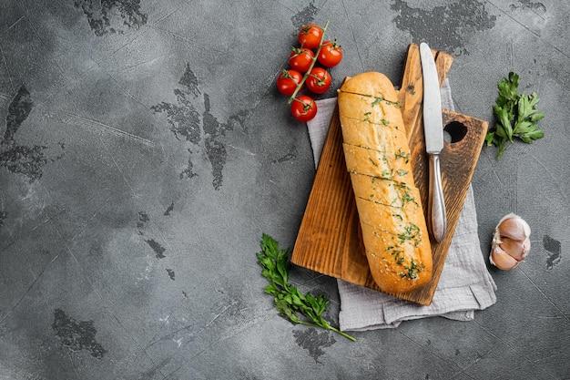 Bagietka z zestawem masła z ziół pietruszki, na szarym tle kamiennego stołu, płaski widok z góry, z miejscem na kopię dla tekstu