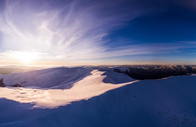 Bajeczna wieczorna panorama z ośnieżonymi górami i wzgórzami z jasnym słońcem i mgłą w mroźny zimowy wieczór