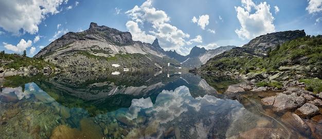 Bajeczne góry i jeziora, podróże i turystyka, bujna zieleń i kwiaty dookoła. rozmrożona źródlana woda z gór. magiczne widoki na wysokie góry, alpejskie łąki