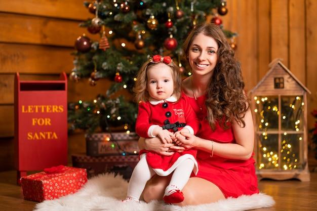 Bajeczne święta bożego narodzenia mama i córka w czerwonych sukienkach zdobią choinkę