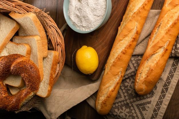 Bajgiel i chleb w koszu z bagietką i cytryną