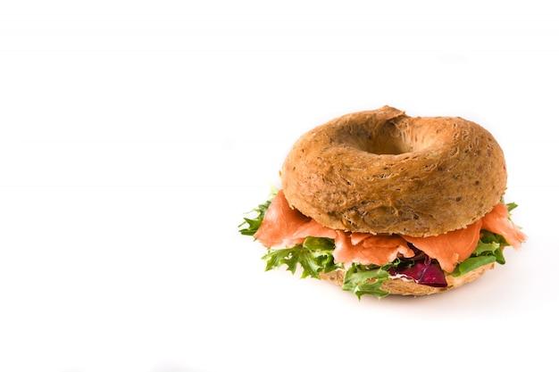 Bajgiel kanapka z kremowym serem, wędzonym łososiem i warzywami odizolowywającymi na białym copyspace