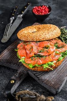 Bajgiel z wędzonym łososiem i serem miękkim, rukola na drewnianej desce do krojenia. czarne tło. widok z góry.