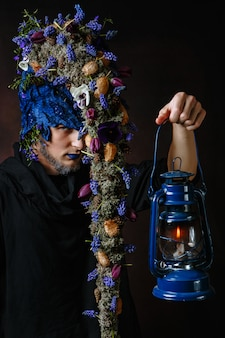 Bajkowa postać o włosach rosnących na gałęziach i kwiatach, która trzyma w środku latarnię ze świecą