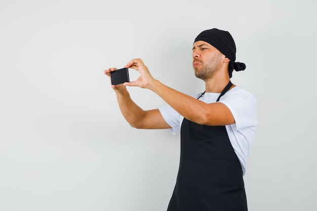 Baker człowiek robienie zdjęć na telefon komórkowy w t-shirt