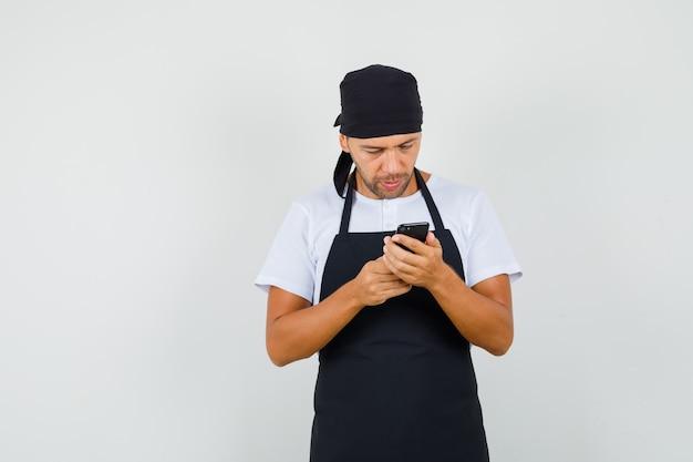 Baker człowiek za pomocą telefonu komórkowego w t-shirt, fartuch i patrząc zajęty
