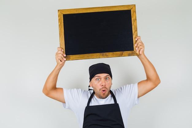 Baker mężczyzna trzyma tablicę nad głową w t-shirt, fartuch i wygląda na zaskoczonego