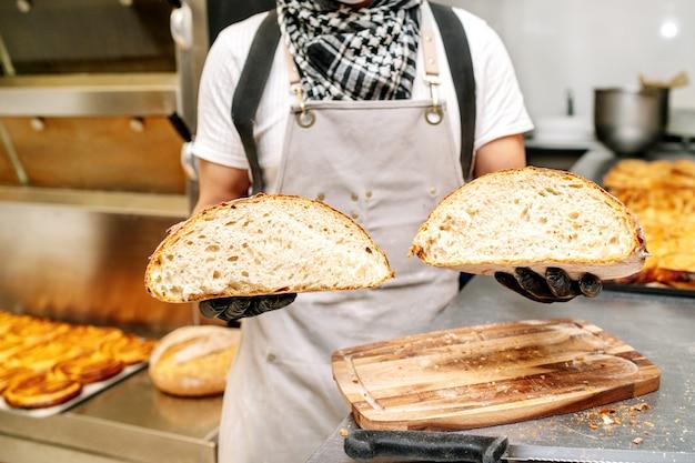 Baker pokazujący rękami okruchy bochenka chleba pszennego i chroniony czarnymi rękawiczkami