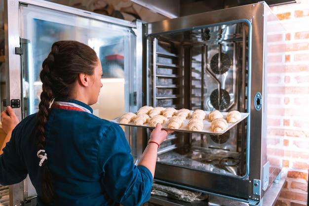 Baker pracuje. profesjonalny, doświadczony piekarz z warkoczem ości typu rybia wkłada do piekarnika blachę z rogalikami