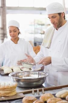 Baker przesiewa mąkę do miski