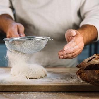 Baker przesiewa mąkę pszenną przez stalowe sito ponad wyrabianiem ciasta