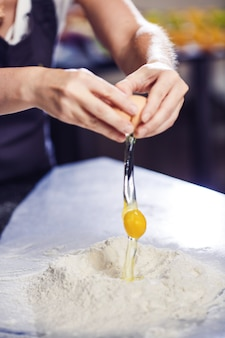 Baker rozbija jajko na kupkę mąki.