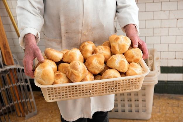 Baker trzyma koszyk świeżo upieczonych bułek