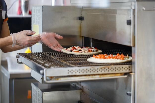Baker wkłada surową pizzę do przemysłowego piekarnika