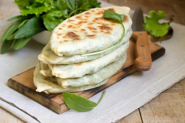 Baker wytwarzający tradycyjne danie ormian z kapeluszy artsakh zhingyalov to rodzaj płaskiego chleba nadziewanego ziołami.