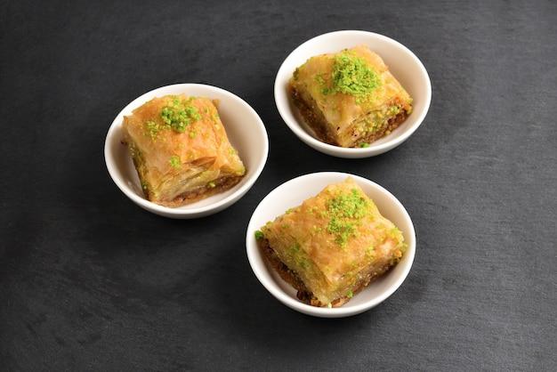 Baklava pistacjowa na czarnym talerzu. deser.