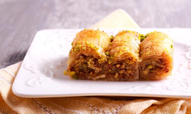 Baklava z pistacjami i miodem na talerzu. żydowski, turecki, arabski tradycyjny narodowy deser.