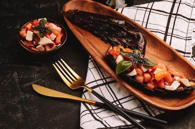Bakłażan pieczony z sałatką pomidorową, fetą i bazylią na drewnianym talerzu