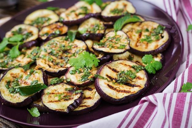 Bakłażan z grilla z sosem balsamicznym, czosnkiem, kolendrą i miętą. wegańskie jedzenie. grillowany bakłażan.