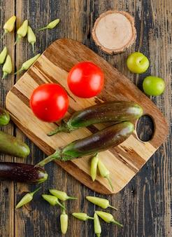 Bakłażany z pomidorami, papryką, zielonymi śliwkami, drewnem na desce i deską do krojenia, płaskie układanie.