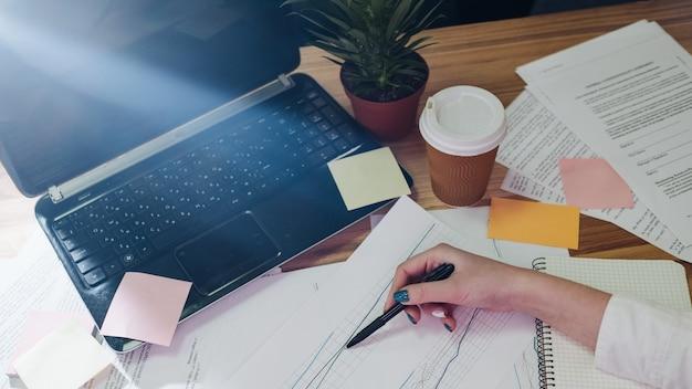 Bałagan na biurku. papiery wykresy umów. zajęty styl życia analityka biznesowego. papierowe karteczki samoprzylepne i notatnik rozrzucone na biurku