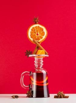 Balance to grzane wino w odwróconym kieliszku na czerwonym tle z dodatkiem cynamonu, pomarańczy i anyżu gwiazdkowatego. jeden z zestawów do grzanego wina.