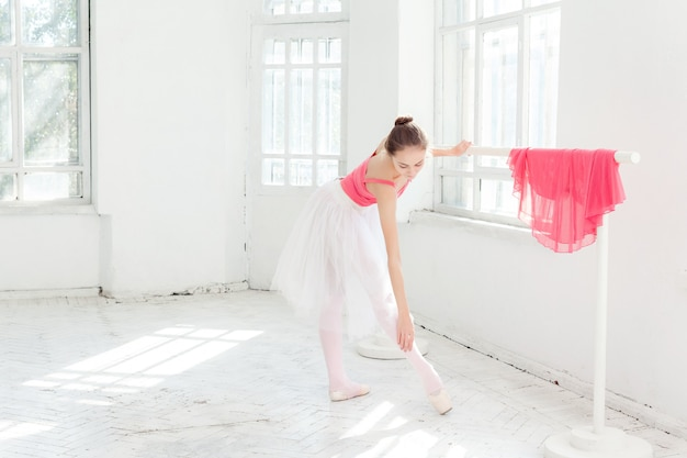 Balerina pozuje w pointe butach przy białym drewnianym pawilonem