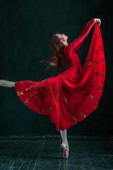 Balerina pozuje w pointe butach przy czarnym drewnianym pawilonem