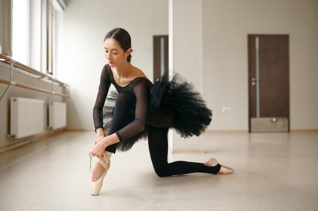 Balerina robi ćwiczenia rozciągające w klasie