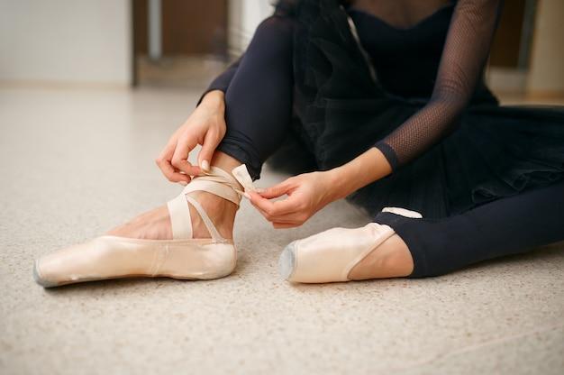 Balerina siedzi na podłodze i zawiązuje wstążkę