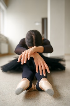 Balerina siedzi na podłodze w klasie, widok z przodu