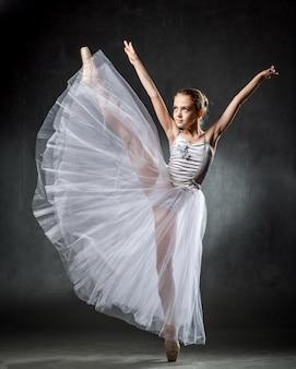 Balerina. śliczna mała dziewczynka pozuje i tanczy w studiu. dziewczyna uczy się baletu. ciemne tło