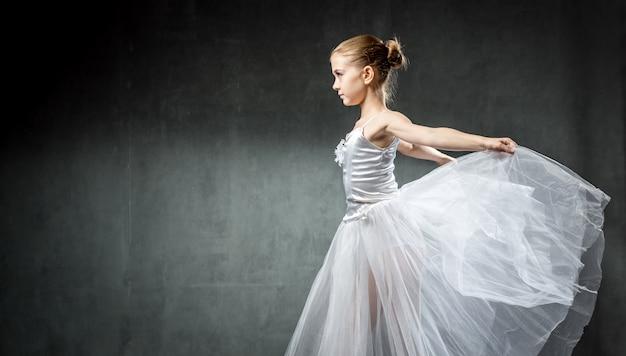 Balerina. śliczna mała dziewczynka pozuje i tanczy w studiu. dziewczyna uczy się baletu.