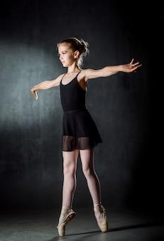 Balerina. śliczna mała dziewczynka pozuje i tanczy w studiu. mały tancerz. ciemne tło czarna sukienka.